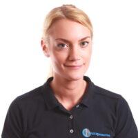 Porträttfotografi av Erika Hallebratt, Kiropraktor, iklädd mörkblå pikétröja med Cityterapeuternas logotyp.