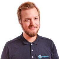 Porträttfotografi av Nils Johansson, Kiropraktor, iklädd mörkblå pikétröja med Cityterapeuternas logotyp.