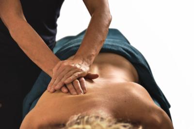 Massörens händer överlappar varandra och masserar djup från skuldran mot axeln.