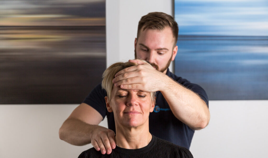 En Naprapat stöttar patientens panna med sin ena hand och pressar med den andra bakom patientens axel