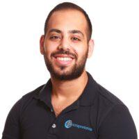 Porträttfotografi av Dani Alkhamisi, AT-Kiropraktor, iklädd mörkblå pikétröja med Cityterapeuternas logotyp.