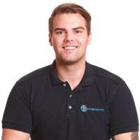Porträttfotografi av Daniel Wilson, Massageterapeut, iklädd Mörkblå pikétröja med Cityterapeuternas logotyp.