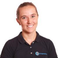 Porträttfotografi av Iselin Bjaanes, AT-Naprapat, iklädd Mörkblå pikétröja med Cityterapeuternas logotyp.