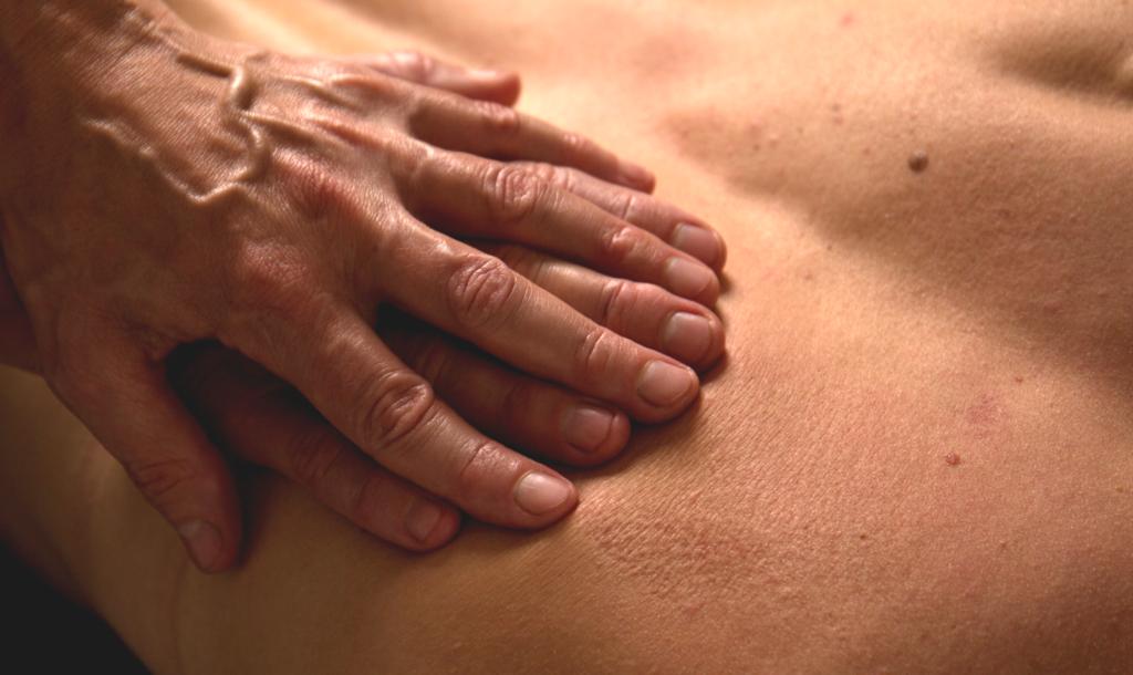 Två händer med fingrarna omlott masserar ryggen med ett brett jämnt tryck